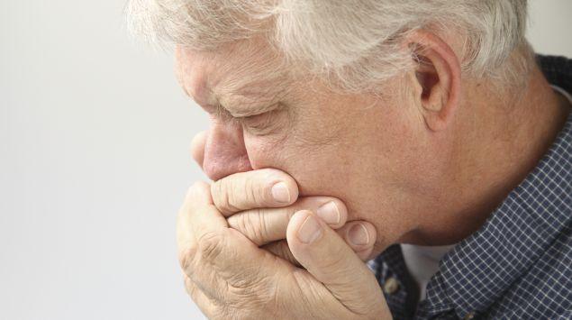 Ein älterer Mann verspürt plötzliche Übelkeit und hält sich die Hände vor den Mund.