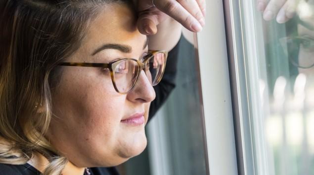 Übergewichtige Frau schaut aus dem Fenster