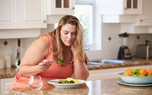 Man sieht eine übergewichtige Frau, die skeptisch ihr Essen betrachtet.