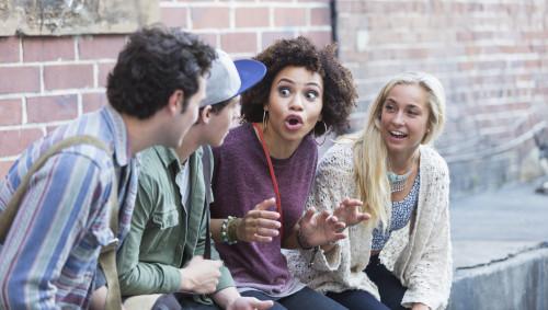 Eine junge Frau erzählt drei anderen Erwachsenen etwas, die Darstellung wirkt übertrieben.