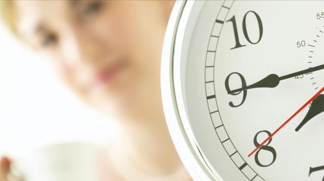 Eine Uhr, im Hintergrund eine Frau mit einer Kaffeetasse.