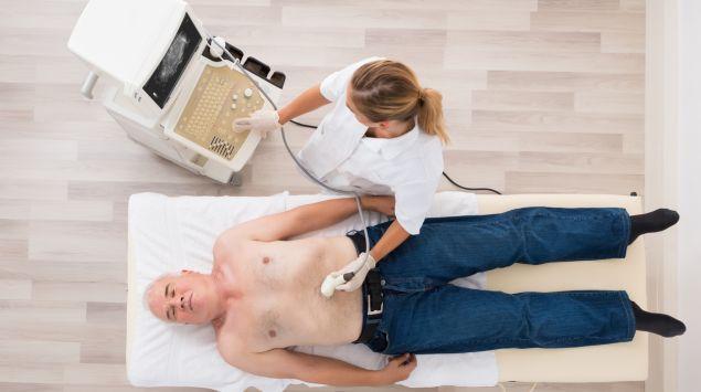 Eine Ärztin führt bei einem älteren Mann einen Ultraschall des Bauchbereichs durch.
