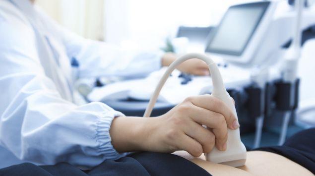 Ein Arzt untersucht den Unterleib einer Frau mit Ultraschall.