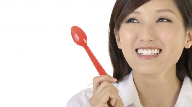 Eine Asiatin hält einen Löffel in der Hand und blickt lachend nach oben.