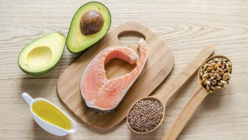 Auf einem Tisch liegen eine aufgeschnittene Avocado, eine Scheibe Lachs, eine kleine Kanne Öl, ein Holzlöffel voller Leinsamen und ein Holzlöffel voller Nüsse.
