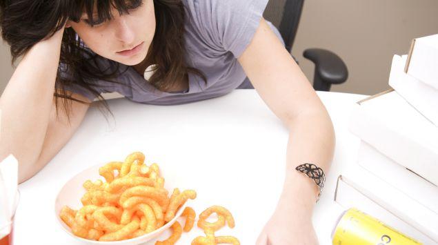 Eine deprimiert wirkende Frau hat eine Schale mit Erdnussflips und eine leere Cola-Dose vor sich.