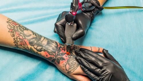 Eine Frau lässt sich an Unterarm und Handrücken tätowieren.