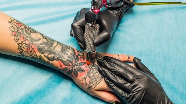 Jemand lässt sich ein Tattoo stechen, was eine Allergie auslösen kann.