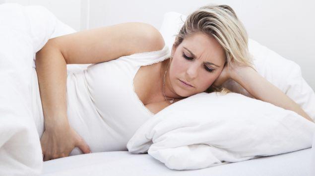Eine Frau liegt mit Bauchschmerzen im Bett.