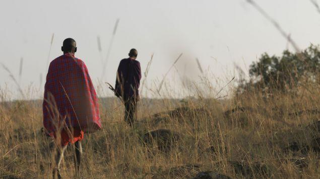 Man sieht zwei Mitglieder von einem afrikanischen Stamm in der Steppe.