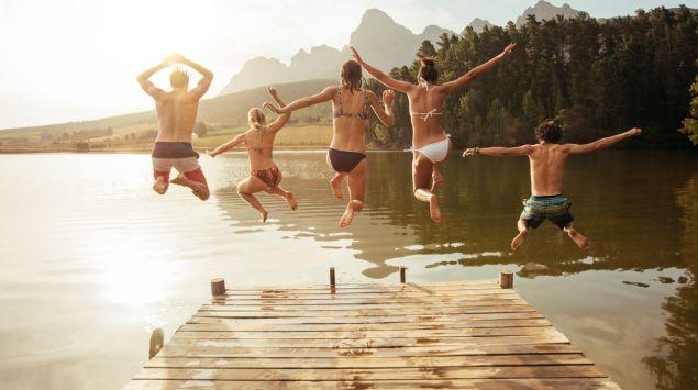 Freunde springen gemeinsam in einen See.