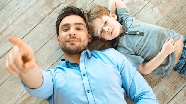 Vater und Sohn liegen nebeneinander auf dem Boden