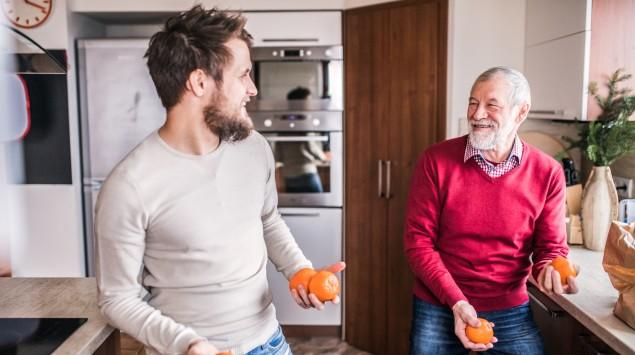 Vater und erwachsener Sohn jonglieren mit Orangen.