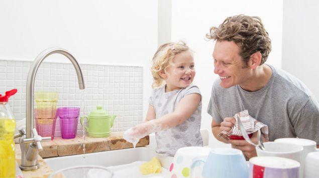 Ein Vater wäscht mit seiner kleinen Tochter ab.