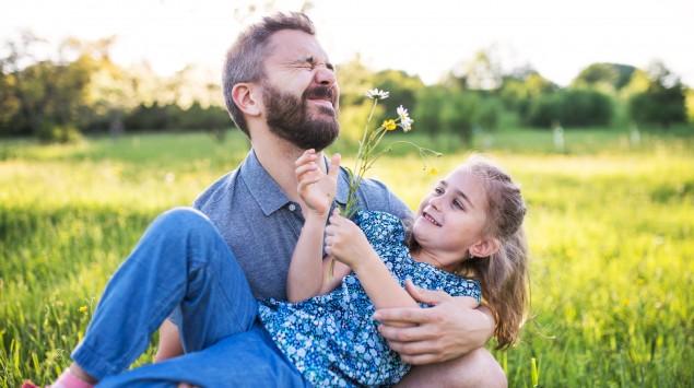 Vater und Tochter spielen mit Blumen