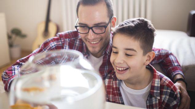 Das Bild zeigt einen Vater mit seinem Sohn, die einen Fisch im Fischglas beobachten.