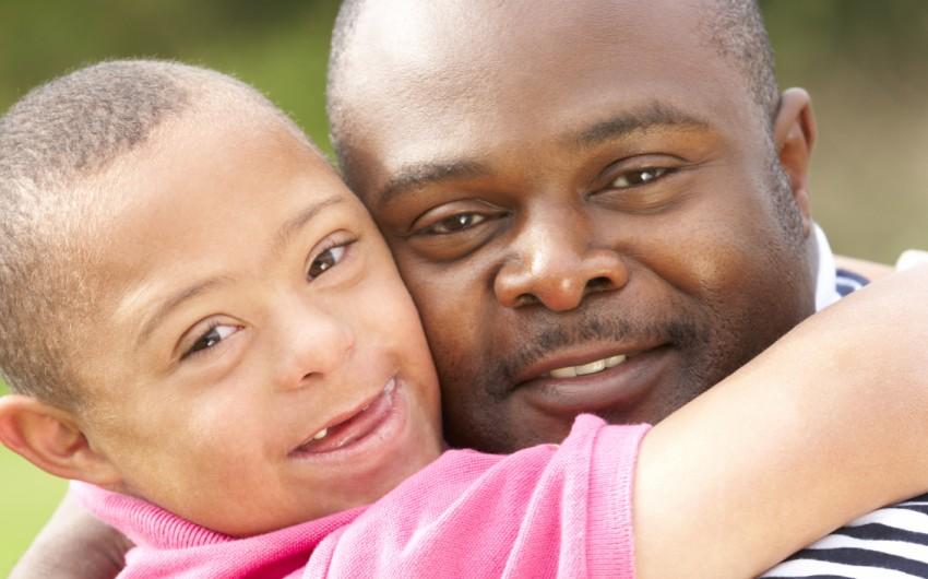 Ein dunkelhäutiger Vater und sein Sohn, der das Down-Syndrom hat, umarmen einander lächelnd.