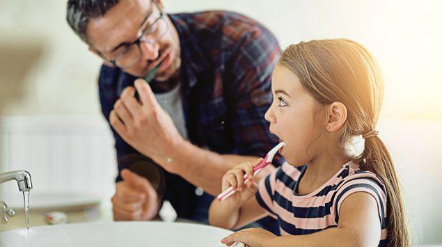 Ein Mann und ein Mädchen stehen an einem Waschbecken und putzen sich die Zähne.