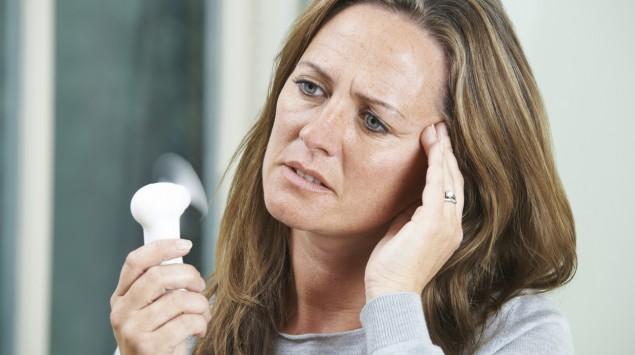 Eine Frau mittleren Alters mit einem Ventilator.