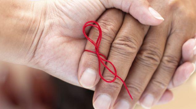 Jemand hält die Hand eines älteren Menschen, am Zeigefinger ist als Erinnerungshilfe ein rotes Bändchen festgeknotet.