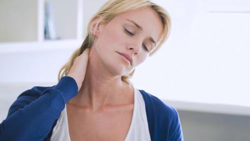 Man sieht eine Frau mit Nackenschmerzen