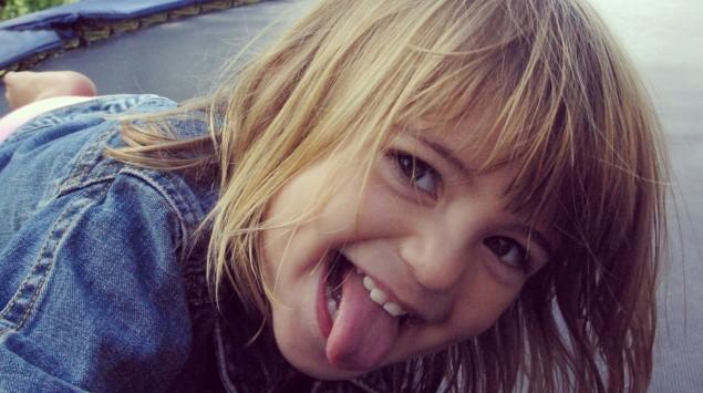 Ein spielendes Kind streckt lachend die Zunge heraus.