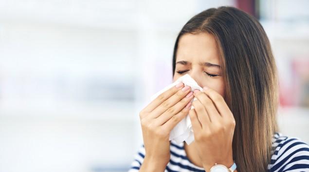 Eine Frau putzt sich die Nase.