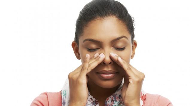 Eine Frau massiert vorsichtig ihr Gesicht links und rechts der Nase im Bereich der Kiefernhöhlen.