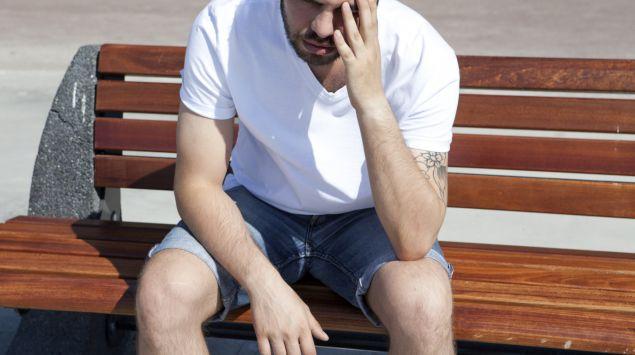 Man sieht einen Mann, der auf einer Bank sitzt und sich den Kopf hält.