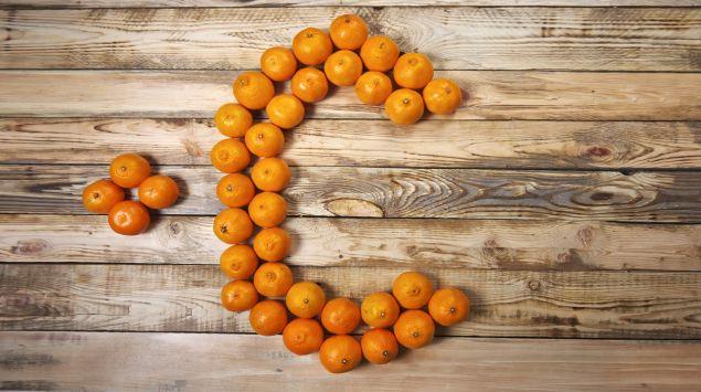 Das Bild zeigt mehrere Orangen auf einem Tisch, die ein C formen.