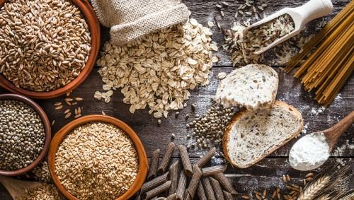 Tisch mit verschiedenen Vollkornprodukten wie Haferflocken, Nudeln und Brot