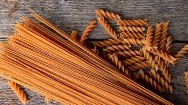 Auf einem Tisch liegen Vollkornspaghetti und -fussili.