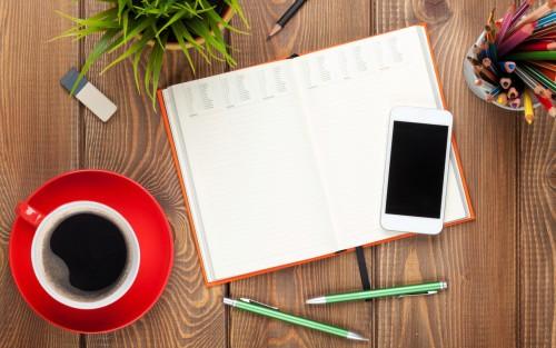 Ein offener Kalender, daneben ein Smartphone, Stifte und eine Tasse Kaffee