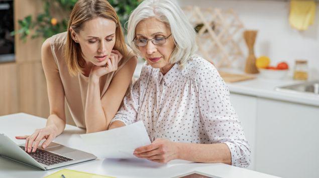 Eine junge Frau schaut sich mit einer älteren Frau ein Dokument an.