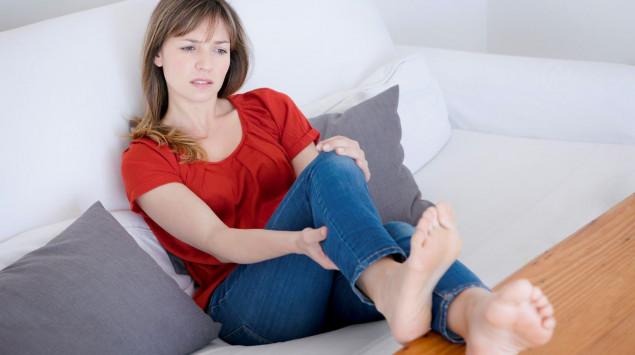 Eine Frau greift sich an die schmerzende Wade. Eine Venentzündung im Bein bildet sich häufig als Folge von Krampfadern.