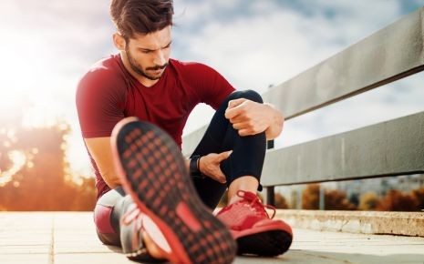 Beinschmerzen: Ein Mann in Sportkleidung sitzt auf dem Boden und hält sich die Wade.