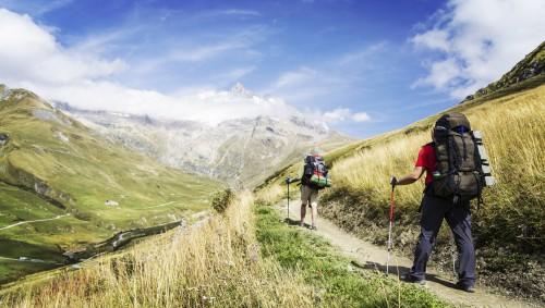 Zwei Personen mit Rucksack wandern in den Bergen.
