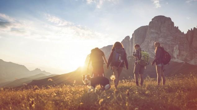 Vier Menschen mit Rucksäcken wandern mit einem Hund über eine Wiese, während die untergehende Sonne hinter einer Felswand verschwindet.