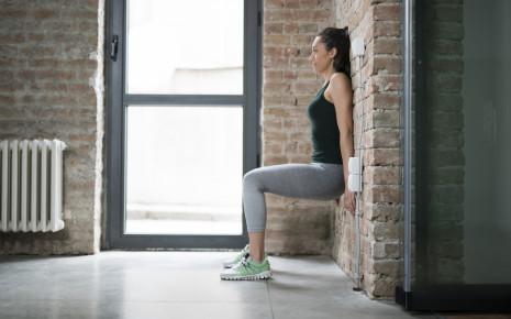 Eine Frau im Sportoutfit macht eine Fitnessübung (Wandsitz).