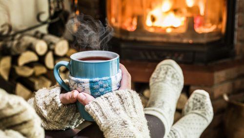Eine Frau mit Socken und heißem Getränk am Kamin.