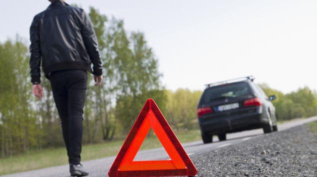 Ein Mann läuft von einem Warndreieck zurück in Richtung Auto.