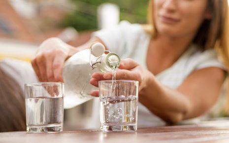 Clean Eating: Eine Frau gießt Wasser in ein Glas ein.