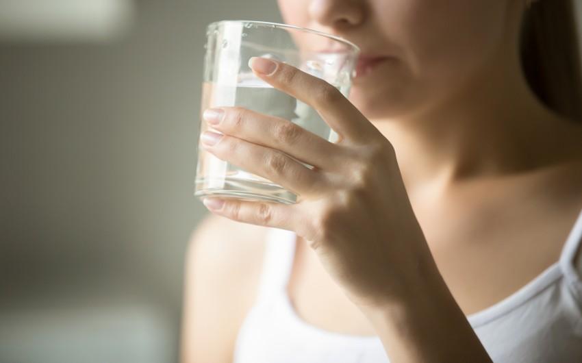 Durchfall: Eine Frau trinkt aus einem Glas Wasser.