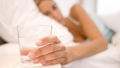 Eine im Bett liegende Frau greift nach einem Glas Wasser.