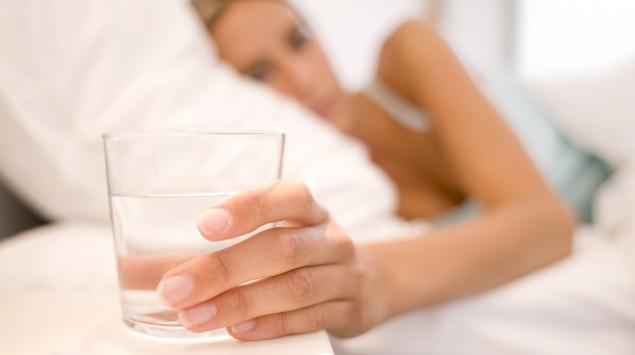 Eine im Bett liegende Frau greift nach einem Glas mit abgestandenem Wasser.