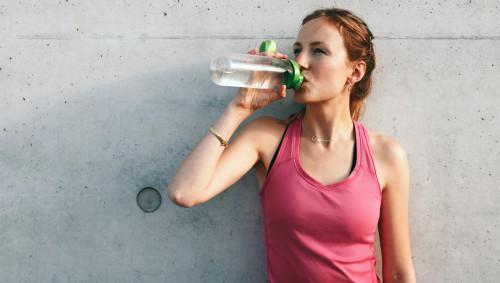 Eine Frau lehnt an einer Wand und trinkt aus einer Wsserflasche.