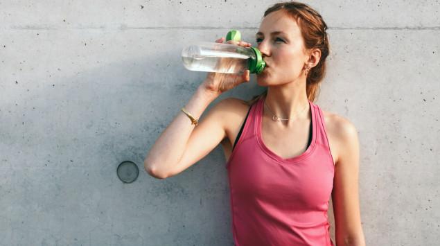 Eine Frau trinkt aus einer Wasserflasche: Kann man Wasser auf Vorrat trinken?