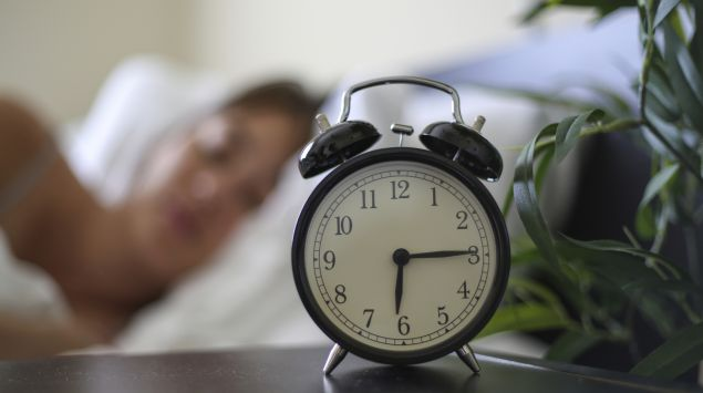 Man sieht eine Wecker auf einem Nachttisch und eine schlafende Frau.