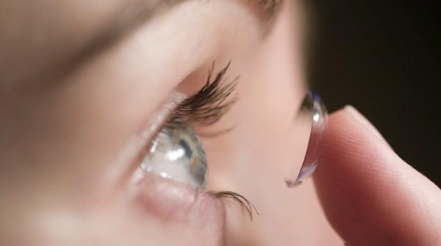 Eine Fraue setzt eine weiche Kontaktlinse ein.