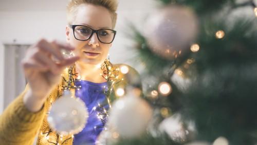 Eine Frau schmückt einen Weihnachtsbaum.